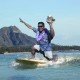 Juan Vargas surfing in front of Diamond Head with Hobee's coffeecake