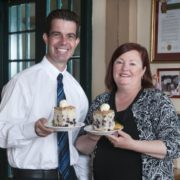 There's only one way to celebrate a Hobee's ownership change -- with blueberry coffee cake. Above, outgoing President Edward Fike and incoming CEO Camille Chijate. (Photo courtesy of Hobee's)